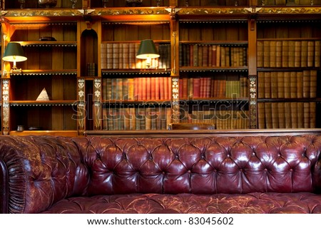 Leather sofa and retro library - stock photo