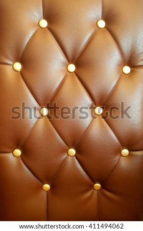 Leather Sofa detail. Vintage brown leather Sofa Button for textured background. Closeup texture of vintage leather sofa. Classic brown leather texture. - stock photo