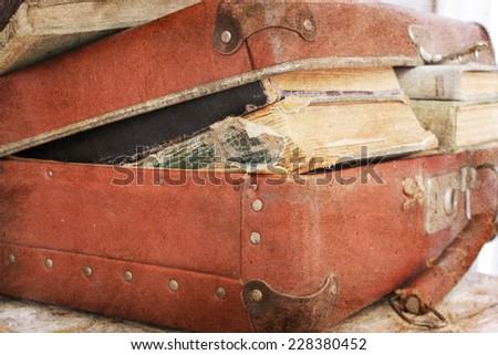 Leather suitcase filled with old books - stock photo