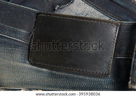 Leather tag on black jeans - stock photo