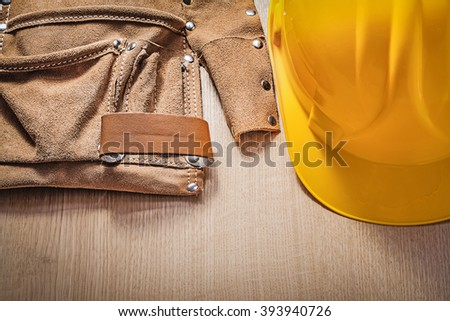 Leather tool belt protective construction helmet on wooden board.