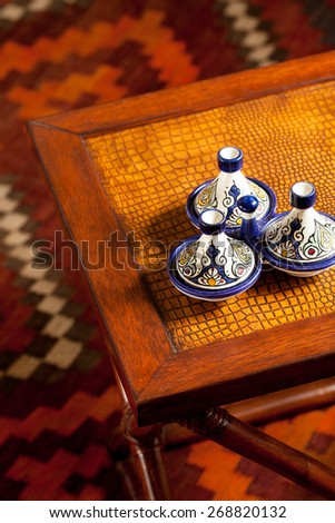 Leather top side table with Moroccan decorative ceramic accessories. Interior close up - stock photo