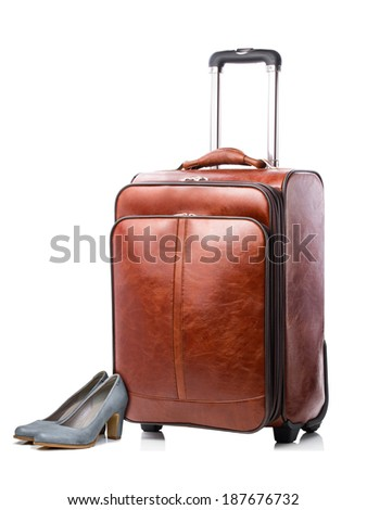 Leather travel suitcase and pair of female shoes isolated on a white background. Travel concept - stock photo