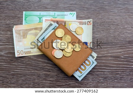 leather wallet with coins and banknotes - stock photo