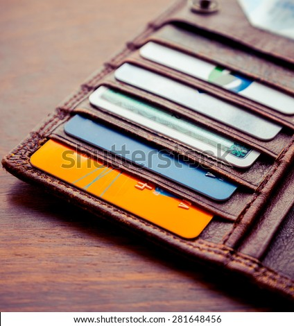 leather wallet with credit and discount cards. Artistic lighting and vintage processing - stock photo