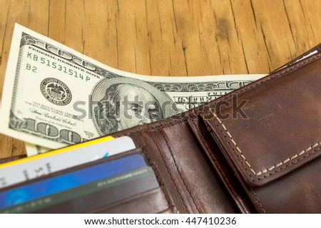 Leather wallet with dollar bills falling out - stock photo