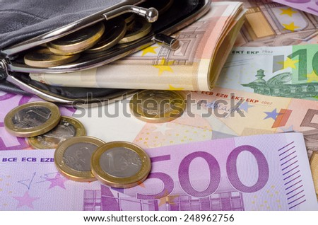 leather wallet with euro banknotes and coins - stock photo