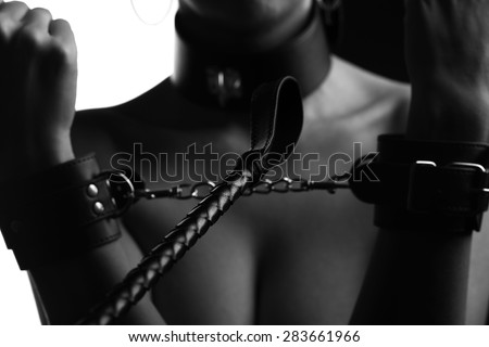 leather whip and a woman in handcuffs, sepia and toning - stock photo