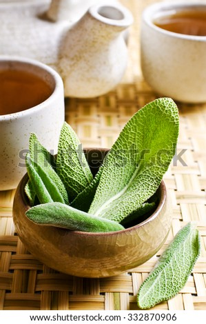 Leaves of fresh sage on a background of ceramic cups with tea - stock photo