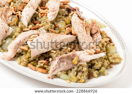 Lebanese cinnamon dusted chicken served on a bed of freekeh fire-dried green wheat with a garnish of toasted nuts. - stock photo