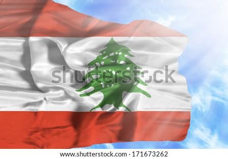 Lebanon waving flag against blue sky with sunrays - stock photo