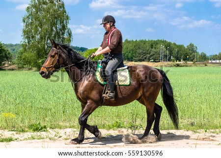 LEBORK, POLAND - May 22, 2016: Man on a horse ride. Riding on rural road through field in countryside scenery