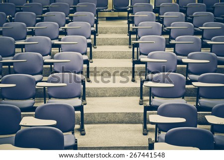 Lecture chairs in a class room with stair path in the middle of a class
