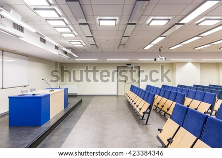 Lecture hall with desk and rows of seats, with navy blue elements