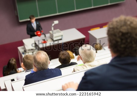 Lecturer at university. Healthcare expert giving a talk to medical faculty professors. Participants listening to lecture and making notes. - stock photo