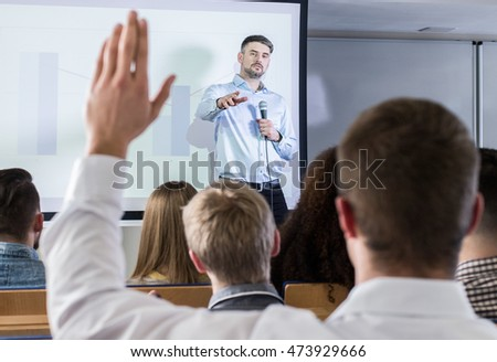 Lecturer point at student who is raising a hand