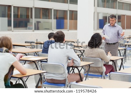 Lecturer talking at top of class in college - stock photo