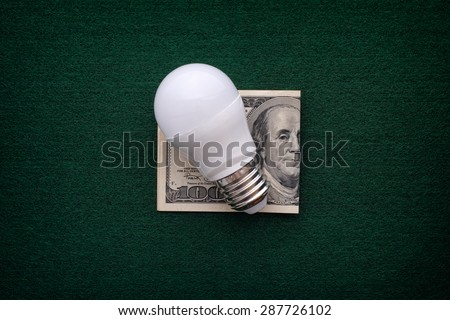 LED bulb and one hundred dollar bill on a green background. - stock photo