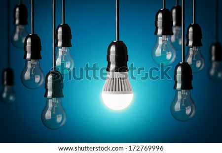 LED bulb and simple light bulbs.Blue background  - stock photo