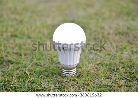 LED Bulb - on the green grass - stock photo