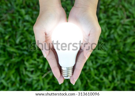 LED bulb with lighting in the human hand with green grass background - stock photo