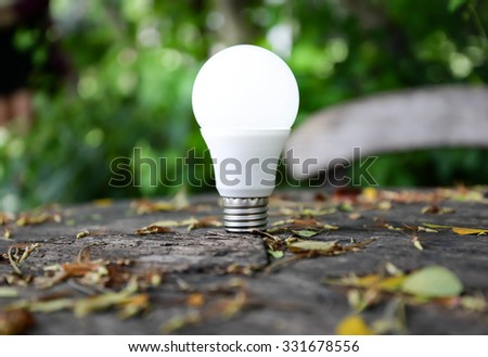 LED Bulb with lighting on nature background - stock photo