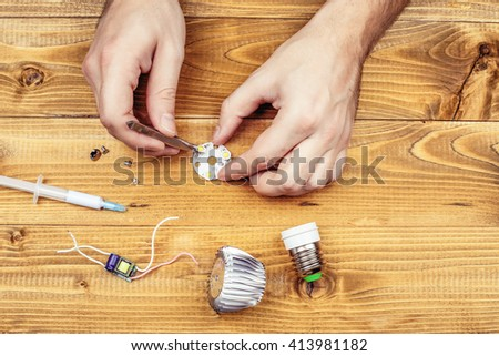 Led lamp with contacts and LED board on a wooden table. Job electrician. Male hands fixing the LEDs lamps. Workplace of electrician. - stock photo