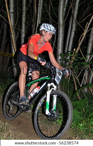 LEDBURY, UK-JUNE 19: An unidentified woman rider at night in the 24 hour 2010 Mountain Mayhem mountain bike competition: June 19, 2010 in Ledbury UK