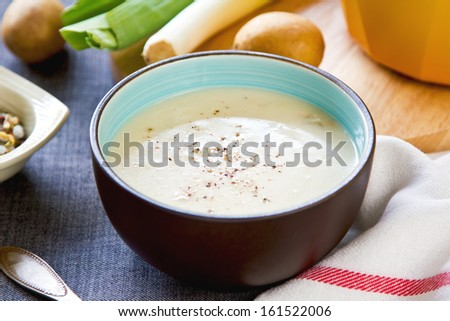 Leek and Potatoes soup by bread and fresh ingredients - stock photo