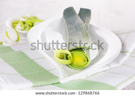 Leek on white wooden textured background. Healthy spring vegetable eating.