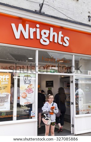 Leek, Staffordshire, England - August 12, 2015: Young girl leaving Wrights family bakers store with take away. - stock photo