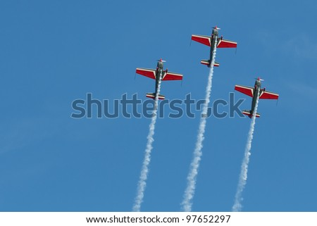 LEEUWARDEN,FRIESLAND,HOLLAND-SEPTEMBER 17: Royal Jordanian Falcons Display Team flying in formation with smoke in their Extra 300L aircraft at the Airshow on September 17, 2011 at Leeuwarden Airfield - stock photo