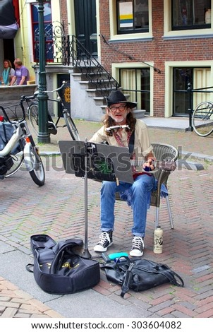 Leeuwarden, Friesland, Netherlands, 24 may, 2014, Hippie is playing music on his guitar and mouth-harmonica during the yearly outdoor Street Festival. In 2018 Leeuwarden is Cultural Capital of the EU - stock photo