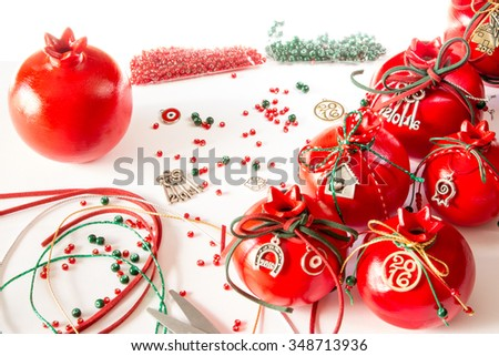 Left ceramic pomegranate, decor elements  beads, ribbons, right pomegranates New Year decorated on white background scattered red, green beads. Preparing for New Year's decoration of pomegranates.  - stock photo