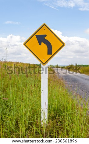 Left curved warning sign with windmill background in wind farm, Korat province in Thailand