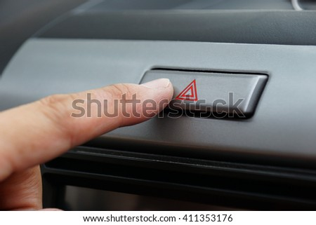 Left forefinger pressing an emergency lights button on car dashboard - stock photo