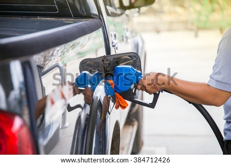Left hand hold fuel nozzle to add fuel in car at filling station.