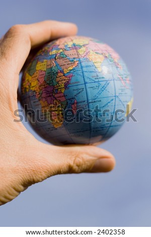 Left hand holding a little globe between fingers. - stock photo