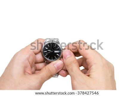 Left hand holding wristwatch and right hand changing time on white background