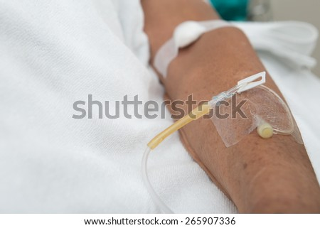 Left hand of the patient on clean bed in the hospital - stock photo