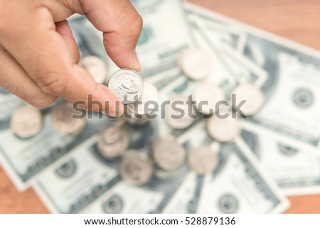 Left hand putting coin to coin stack, saving money concept.