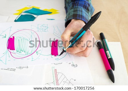Left handed designer making a rough sketch of a system solution during the product design process  - stock photo