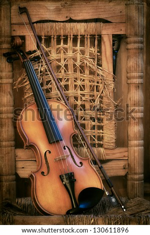 Left handled Violin lying on an old and ruined chair - stock photo