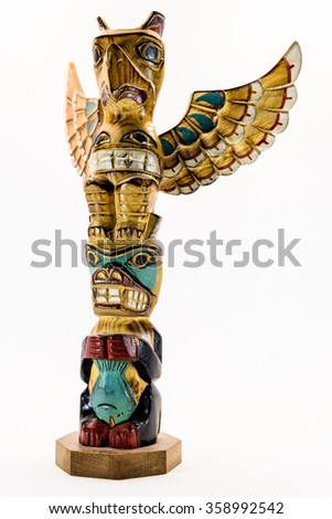 Left side slight profile of a carved wooden American Indian eagle and wolf Totem Pole with wings isolated on a white background - stock photo
