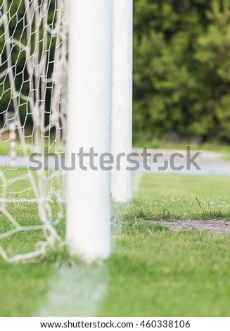 left side view of standard goal and net in football pitch or soccer field, sport equipment in the stadium - stock photo