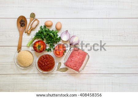 Left tomatoes, onions, parsley and beef minced meat, bread crumbs, red sauce, spices on light wood background, right empty space. Prepared ingredients for cooking differently minced meat. Top view. - stock photo