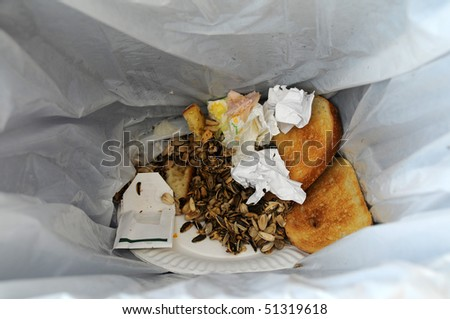 Leftover food and trash in a garbage bin - stock photo