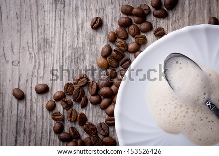 Leftovers of coffee foam on saucer with spoon placed on wooden background with coffee beans. Flat-lay with copy-space. - stock photo