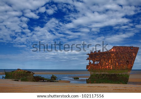 Leftovers of the old rusty ship on the coast of a ocean - stock photo
