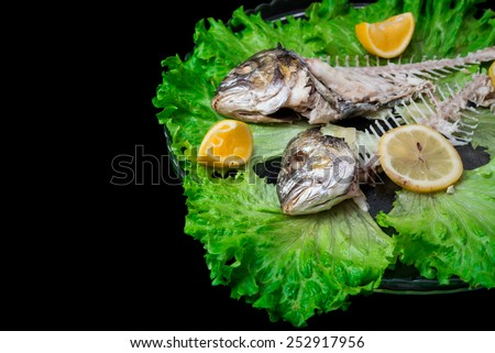 Leftovers of two baked dorados with squeezed lemons and green lettuce - stock photo